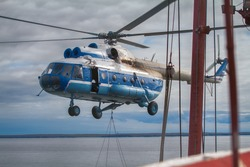 Ship-based helicopter takes off from deck of icebreaker, sling load operation