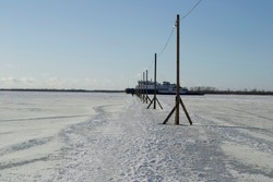 ship breaks ice on a frozen river for other ships. crosses a pedestrian crossing to the other side