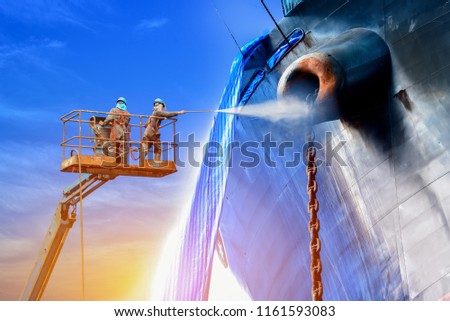 Ship cleaning by Worker two man with safety harness used pressure washer cleaning ship on Trucks have sherry piker, the success of the work in factory #1161593083
