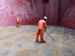 ship crews are brushing cargo hold tanktop on bulk carrier during hold cleaning. preparation for grain loading.