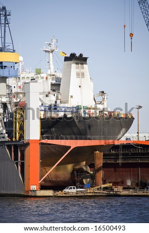 ship in dry dock - large container ship rear view with propeller under repair