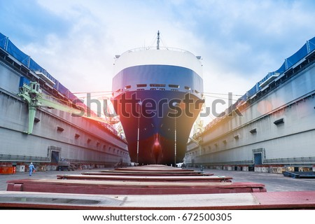 Photo of  ship in floating dry dock under repair by sandblasting and painting in shipyard