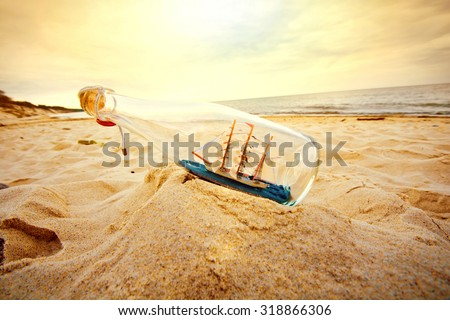 Stock Photo Ship in the bottle lying on the beach. Souvenir conceptual image. Nature in paradise.