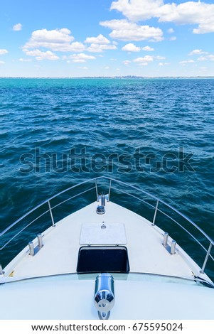 Ship in the sea before the shore. Swimming by ship in the sea, sunny day, sky with clouds. The nose of the boat on the water. #675595024