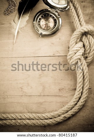 ship ropes and compass at wood background on sepia