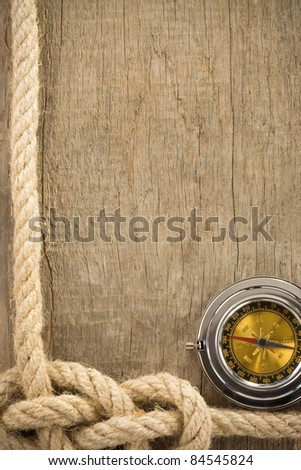 ship ropes and compass on wooden background texture