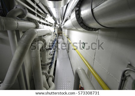 Ship's Engine Heavy Machinery Space - Pipes, Valves, Engines.Shipyard industry ,( ship building) Big ship on floating dry dock in a shipyard located at Port Klang , Malaysia #573308731