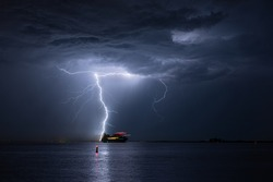 Ship sails across a river during a severe lightning storm