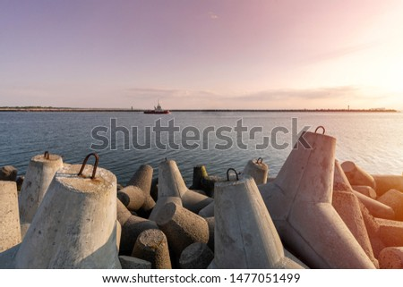 Ship-tugboat goes in high seas to tow cargo ship to port. Beautiful sunset over the pier. Tetrapod breakwaters in harbor. #1477051499