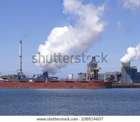 ship unloading in front of a large steel factory in IJmuiden, Netherlands