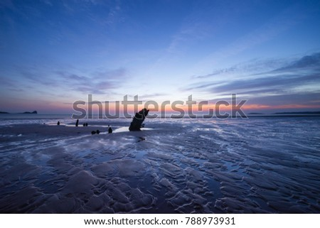 Ship wrack remains in the twilight on Rhossili Bay beach, Wales #788973931