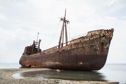 Ship wreck surrounded by sea waves on moody Selinitsa beach, Gytheio, Greece