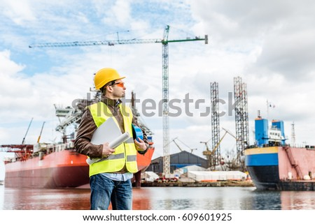 Shipbuilding engineer stands at the dockside in a port. Wearing safety helmet, yellow vest and safety glasses. Shipbuilding industry.