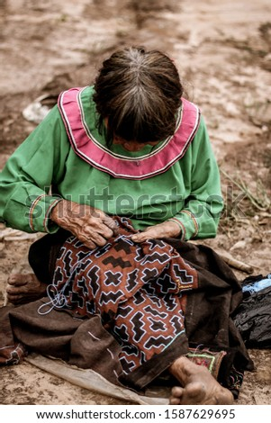Shipibo artisan looking down with a embroidery textile