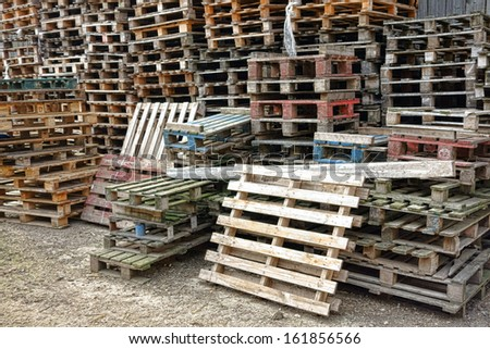 Shipping and transportation wood pallets in stacks waiting for bulk recycling in a freight warehouse shipment yard