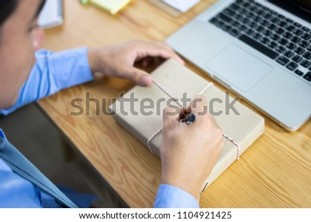 Shipping shopping online ,young start up small business owner writing address on cardboard box at workplace. seller prepare parcel boxs of product for deliver to customer.Online-selling or e-commerce