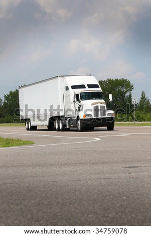 shipping truck driving down road on blue sky #34759078