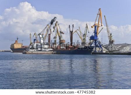 Ships and cranes in cargo port. Black sea, Feodosia, Ukraine.