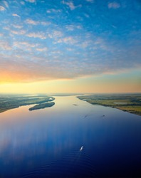 Ships are on the great river during white nights. On the river is calm now. A boat cuts through the waters of the great river.