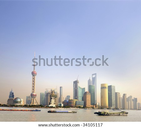 Ships at sunset on the Huangpu River in Shanghai,China. At the background the financial district with skyscrapers and the Pearl Tower.