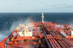Ships bow and rainbow in spraying sea water - stock photo