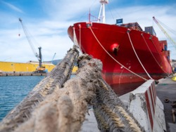 Ships mooring ropes, view from the bollard, wit a focus on a front point and ship not in focus in the background