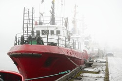 Ships, tugboats and fishing boats (trawlers) moored to a pier in a harbor. Thick white fog. Latvia, Baltic sea. Panoramic view. Service, repair, freight transportation, logistics, industry, commerce