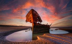 Shipwrecked off the coast of Ireland, An shipwreck or abandoned shipwreck,,boat Wreck Sunset light at the beach, Wrecked boat abandoned stand on beach or Shipwreck