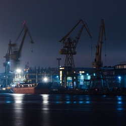 SHIPYARD AT NIGHT - Ship at the quay and a slipway with cranes