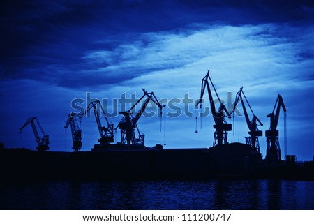 Shipyard cranes against blue sky, artistic toned photo
