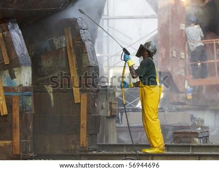 shipyard worker powerwashing a ship on drydock