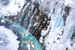 Shirahige waterfall and blue pond in winter at Taisetsuzan National Park,Hokkaido,Japan.Beautiful outdoor scene landscape with frozen snow and ice.