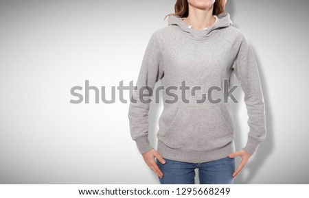 Shirt design and fashion concept - young woman in gray sweatshirt, gray hoodies, blank isolated on grey background. mock up