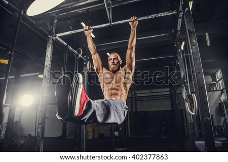 Shirtless bearded man doing stomach exercises on a horizontal bar.