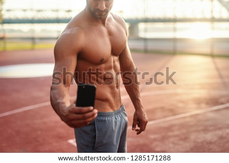 Shirtless Caucasian sportsman taking selfie while standing on the court in the morning.