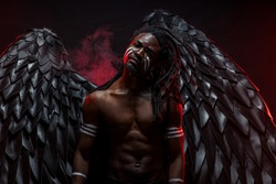 shirtless dark angel isolated in red smoky space, young muscular angel come down from heaven for mission. angelic devil emotionally posing at camera, isolated space with red neon lights