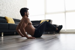 Shirtless fitness instructor performs a knee tuck exercise at home. Muscular young good looking white male is working out on the floor of his house doing an ABS routine and training his core muscles.