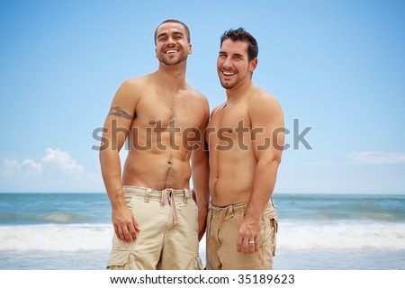 Shirtless gay couple standing on a beach