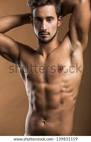Shirtless male model posing over a brown background