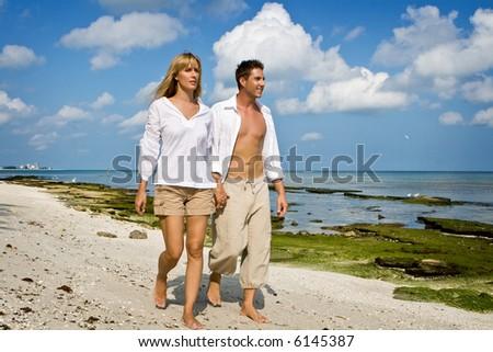 shirtless man and female walking at the beach