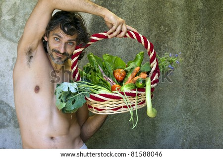 shirtless man with a basket of harvested vegetables