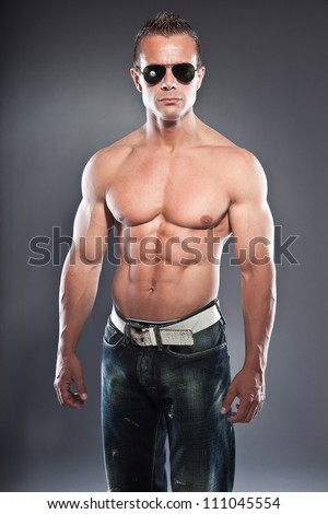 Shirtless muscled fitness man. Cool looking. Tough guy. Blue eyes. Blond short hair. Wearing black sunglasses. Tanned skin. Studio shot isolated on grey background.