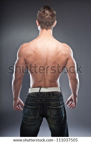 Shirtless muscled fitness man showing his back. Cool looking. Tough guy. Blue eyes. Blond short hair. Wearing black sunglasses. Tanned skin. Studio shot isolated on grey background.