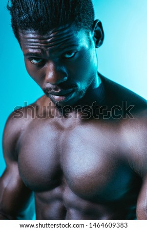 shirtless, muscular african american sportsman looking at camera on blue background
