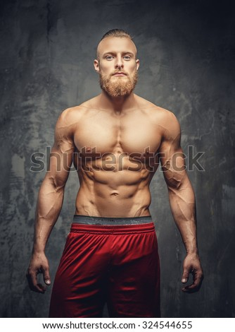 Shirtless muscular bearded man in red pants posing in studio over grey background.