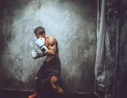 Shirtless muscular fighter in action. Isolated on grey background.