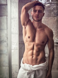 Shirtless muscular handsome man looking at himself in bathroom mirror in the morning after shower or bath, with towel around his waist