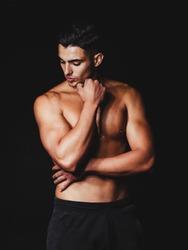 shirtless muscular man on a black background