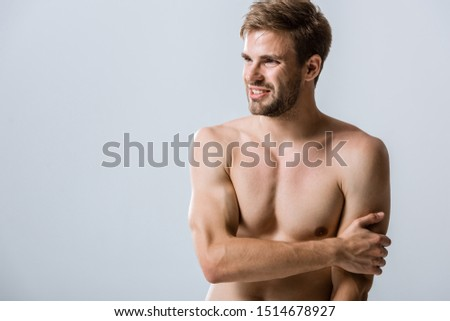 shirtless muscular man with pain in arm isolated on grey