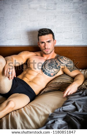 Shirtless muscular sexy male model lying alone on bed in his bedroom, relaxing with eyes closed